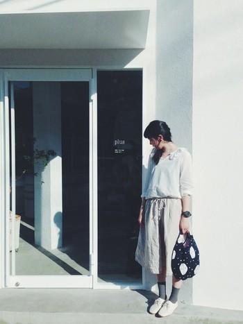 白いブラウスにベージュのロングスカート、グレーのソックスと、淡い色同士を組み合わせたナチュラルスタイル。ミナ ペルホネンのバッグが全体を引き締めてくれています。