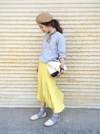 明るいイエローのプリーツスカートに、トップスとソックスをライトグレーで揃えた上品なコーデ。女性らしいふんわりとした雰囲気が可愛らしい。