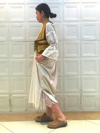 ワンピースのスリットからは、レース素材のスカートが覗きます。オフホワイトのワンピースを着たナチュラルコーデにはボヘミアン調のベストがよく似合いますね。