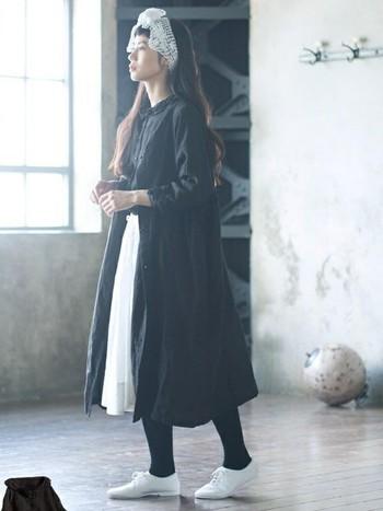 ブラウスをロングスカートにタックインしたフェミニンなスタイルに、ボタン付きのワンピースをさらりと羽織って。なんだかお人形さんみたいな、クラシカルな雰囲気のモノトーンコーディネートです。