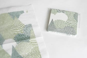 可愛らしい森のテキスタイルがプリントされた「点と線模様製作所」のナプキンとコースター。風に揺れる一枚一枚の葉を、点描で表現しています。
