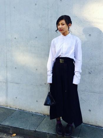 白シャツとデザイン性の高い黒のロングスカート。シンプルなはずなのにすごく個性的に仕上がっているのは、ベルトやバッグの少し尖った印象と、上までカッチリボタンを留めたシャツとのギャップのせいでしょうか?きちんと計算されたオシャレ上級者スタイルはお手本にしたいですね。