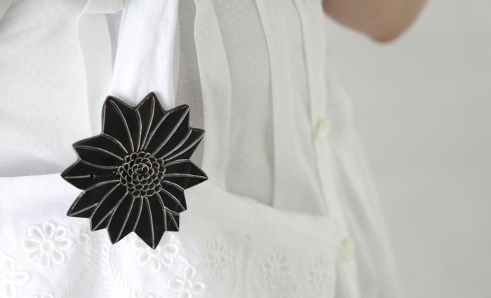 ■Si-Si-Si│山菊  水牛の角を彫って繊細に表現された、山菊のブローチ。 艶のある深い黒の中に、天然素材ならではの微妙な色の重なりを見ることができます。 シックな装いにはもちろん、あえてカジュアルな服に合わせても素敵。