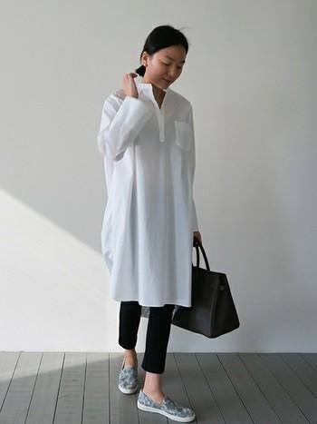 白のロングシャツに細身の黒のパンツを合わせて。バッグまで黒でまとめれば、上品な大人の着こなしが光ります。足元は、あえてスリッポンで外して遊び心を持たせても◎。
