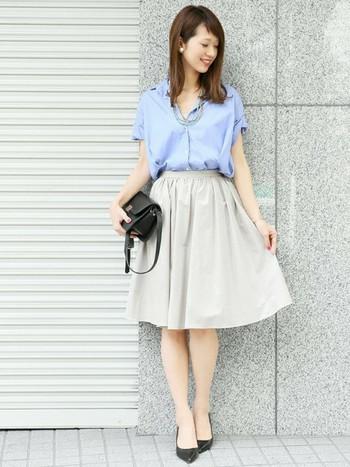 ふんわりしたギャザースカートで女性らしさアップ。ブルーのブラウスを合わせて爽やかに。
