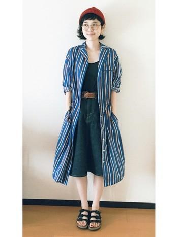 シンプルなシャツ、リジットデニムのスカートはorslow (オアスロウ)のもの。個性的なシャツワンピを羽織って、こなれ感のあるナチュラルカジュアルです。