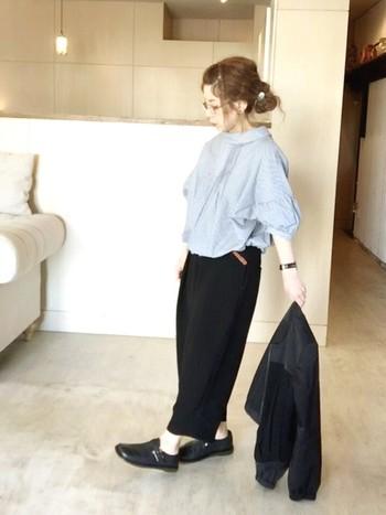 ふんわり、バルーン袖のブラウスは爽やかなブルーで素敵。ほかの色を黒で統一することで、引き立っていますね。ベルトや時計、メガネにこだわりを感じます。