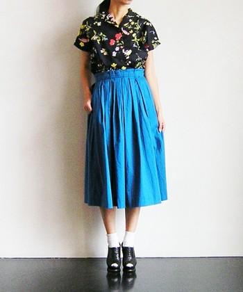 鮮やかなブルーが夏を連想させるようなスカート。トップスは黒の大きめ花柄を合わせて個性的に。