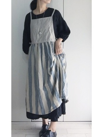 スカート部分が爽やかなストライプになったエプロンワンピース。インナーに黒のワンピースを合わせると、ナチュラルながらも大人っぽい雰囲気に。
