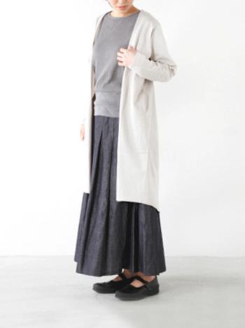マキシ丈のデニムスカートに、コンパクトなライトグレーのトップスを合わせたコーディネート。ボリュームのあるロングカーデガンも、白を選ぶことで重たくなくなります。
