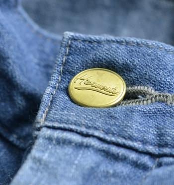 ブランドロゴがあしらわれたオリジナルボタン。随所に見られる丁寧な縫製・・・。ポケットについている真鍮のブランドロゴプレートは手作業で付けているんだとか。