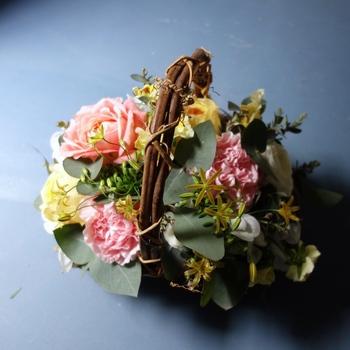 カーネーションを主役に、ピンクとイエローの花をきゅっと詰め込んだ[S]サイズ。ころんとまるいシルエットで、お部屋を愛らしく彩ります。