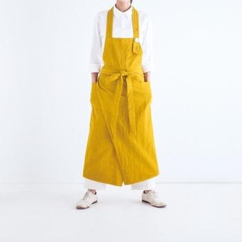 厚手のオーガニックコットンが頼もしい草木染のエプロン。鮮やかな黄色はマリーゴールドを染料にしています。