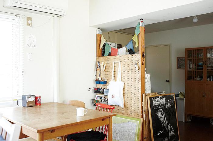 パーテーションを作ってキッチンとリビング部分の間仕切りに。有孔ボードにフックやワイヤーラックを取り付けると細々したものの収納もできて便利です。