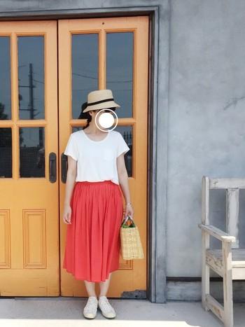 南国に咲くハイビスカスのように美しい赤のスカートを主役にした、着ているだけで元気になれそうなコーディネート。麦わら帽子とかごバッグがナチュラルにまとめてくれています。