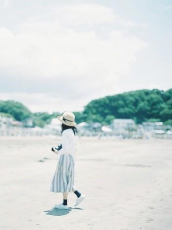 ホワイト×ブルーで初夏にぴったりのさわやかなコーディネートには、麦わら帽子がマスト。足元は同系色のネイビーで引き締めることで、バランスの良いコーディネートになります。砂浜がとっても似合いますね。