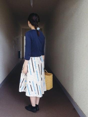 かわいらしいレトロ柄のスカートを主役にしたスタイル。ちょっぴりモードで個性的な雰囲気をかごバッグが程良くほぐして、バランスの良いコーディネートになっています。