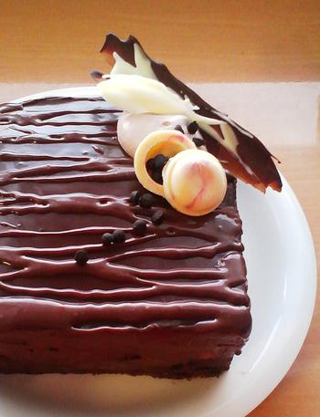 ガナッシュクリームを全面に塗ったチョコレートケーキを作ったものの、時間をかけすぎて塗りムラができてしまったり、きれいなツヤが出なくてがっかり…という時の裏ワザがこちら。残ったガナッシュを牛乳や生クリームで少し柔らかめに伸ばし、ケーキの上に垂らして模様にしてしまいます。これで、下地のガナッシュの塗りムラはほとんど目立ちません。(筆者撮影)