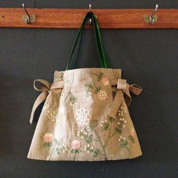 なんとデイリーに使えるバッグもお目見え。オリジナルの模様を刺繍したリボンバッグ。リボンを大きく両脇に結んで、A4サイズもすっぽり入る四角い形にも変えられます。ポケットは背面に1つ、内側にも2つ付いており、機能性にも備えた優れモノです。