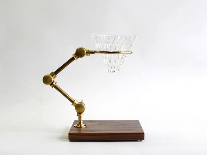 実験器具と勘違いしてしまいそうなこちらのアイテム、実はドリッパースタンドなんです。 ウォールナットと真鍮素材を組み合わせたクラシカルな佇まいと、コーヒーツールとは思えない美しい造形は、まるでアート作品のよう。 日本のメーカーHARIO(ハリオ)の耐熱式V60ガラスドリッパーが付属しています。