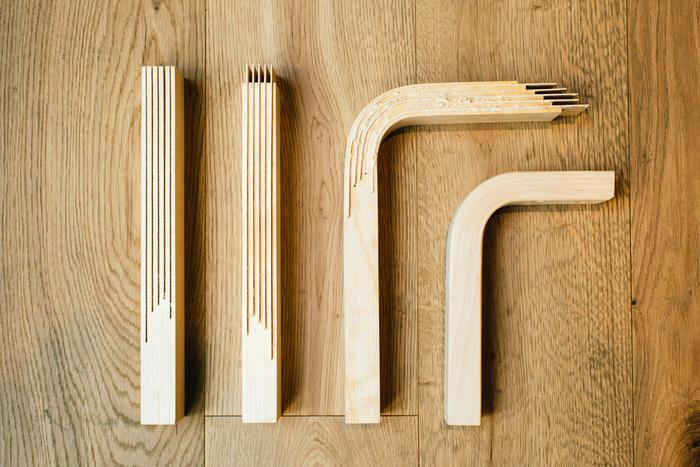 L - レッグの制作過程がわかるパーツ。無垢の木にスリット(割れ目)をミリ単位で入れ、その間にベニヤ板を挟みます。プレス加工を施しながらL字型に曲げ、最後に人の手により隙間を木屑で埋め、磨きをかけて完成します