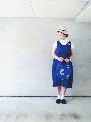 ブルーのノースリーブワンピースと丸襟のブラウスで、少女のように可憐なコーディネート。テキスタイルの施されたブルーのバッグを合わせて、統一感のあるアクセントを。