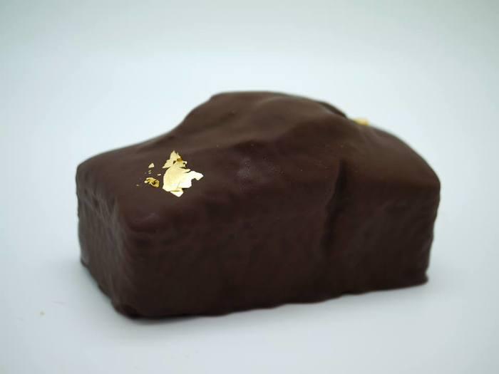 静寂のワルツ -オペラのパウンドケーキ-  コーヒー生地にフランス・ヴァローナ社の粒チョコレートを散りばめ、焼成、コニャックとシロップに浸した後、まるごとチョコレートでコーティングし、金粉を添えた作品です。このパウンドケーキはジャズピアニスト、ビル・エヴァンスへのオマージュとして作られた一品です。