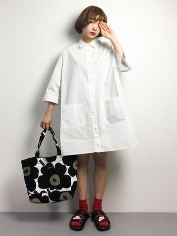 白のビッグシャツワンピに赤ソックスのみという目を引くスタイル。大きな柄が特徴のマリメッコのモノトーンバッグともよく合います。