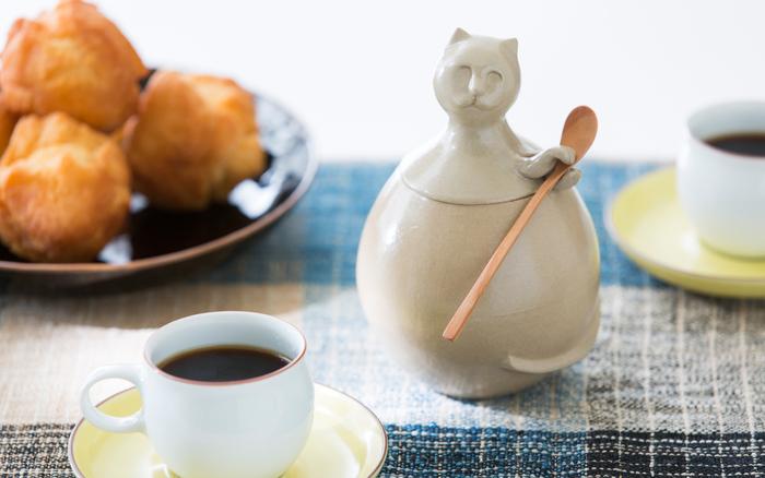 沖縄で昔から日常的に使われている「やちむん」と「きび砂糖」をセットにしたアイテムです。サトウキビから作られる「きび砂糖」は、沖縄県産のもので、合わせている黒糖も沖縄の離島各地のものを使用しています。特別な配合で作られている「きび砂糖」は、口当たりが滑らかで、上品なまろやかさが魅力です。 セットになっている沖縄の陶器「やちむん」はイリオモテヤマネコをモチーフにした、デザイナーのキギさんのオリジナルのデザイン。ざっくりとした手触りと素朴なフォルムが食卓の印象を温かくします。
