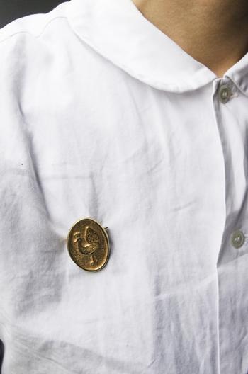 メダル型で、ちょっぴりアンティークな雰囲気のブローチは、丸襟など、クラシカルなシルエットのシャツにぴったりです。