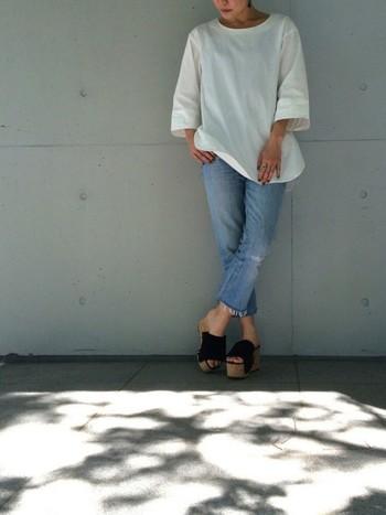 七分袖のゆったりとしたホワイトスモックシャツにリーバイスのカットオフデニムを合わせた70sの意識した爽やかなリラックススタイル。足元はプラットフォームサンダルで女性らしさがプラスされています。