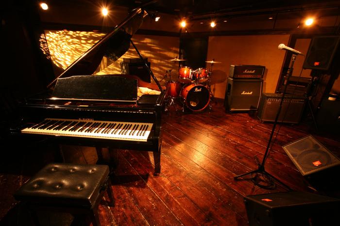 重厚感を感じさせる広々としたステージにはグランドピアノが!他のライブハウスとは一味違った演出も味わえそうです。