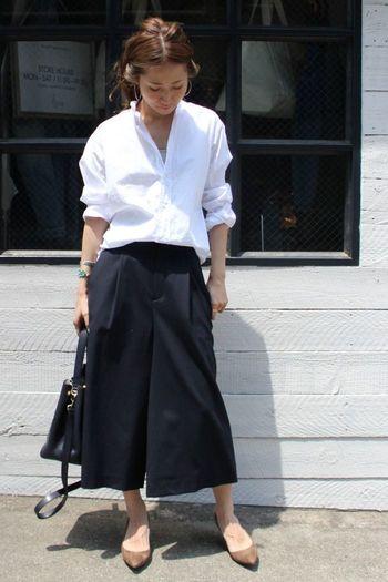 """シックなワイドパンツが眩しい白シャツを引き立てる清潔感のあるモノトーンコーディネート。ゆったりしたサイズ感のシャツをボトムスにインすることで""""こなれ感""""が生まれます。落ち着きのあるシンプルなコーディネートはオフィスファッションにもぴったりです◎"""