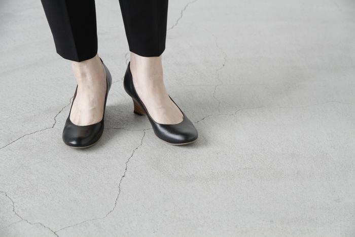 """黒のパンプスは、いかにも""""お仕事用""""で味気ない。このパンプスなら、きちんと感もありながらおしゃれも両立できるので、きっとお気に入りの一足になるはず。ころんとした丸いラウンドトゥも愛らしく、黒でも優しい印象になりますよ。やわらかなインソールで歩きやすく、長時間履いても疲れにくいのもうれしいポイント。"""
