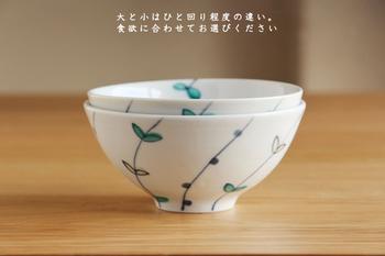 九谷青窯の若手の陶芸家、高 祥吾さんの作品は、初々しい葉っぱと、瑞々しい実がなった様子が描かれたお茶碗。高台から伸びる枝の中に、一枝だけお碗の淵を乗り越え、内側にも葉っぱが顔を覗かせています。ちょっと楽しい、遊び心が隠れたお茶碗です。