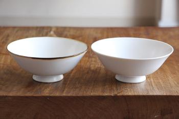 創業350年の有田焼の窯元が、生活用品デザイナーの大治将典さんを迎え、2012年に新たに立ち上げたブランドが「JICON・磁今」のシンプルなお茶碗は、どことなく愛嬌のあるかたちが魅力的。「渕鋼」と「白」の二種類のお茶碗は、よく見ると釉薬の流れた跡や、小さな気泡、材料に含まれているという小さな鉄分の斑点なども見られ、職人の手仕事によって、いくつもの行程をこなしている、その様子が目に浮かぶ様です。