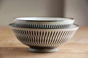 """大分県日田市の山あい、皿山を中心とする小鹿田地区で焼かれる陶器、""""小鹿田焼""""は、国の重要無形文化財にも指定され、300年もの歴史があります。小鹿田焼きの代表的な技法のひとつ「飛び鉋(かんな)」を施したこのお茶碗は、象ったお茶碗に化粧土をかけ、ロクロを回しながら鉄の鉋の先をあて、化粧土を削って鉋の跡をつけていきます。素朴で温かみのある雰囲気のお茶碗は、モダンな印象にも見えます。"""