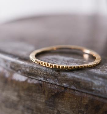 極細のデザインが、女性の華奢な指先をさらに美しく見せてくれるゴールドリング。