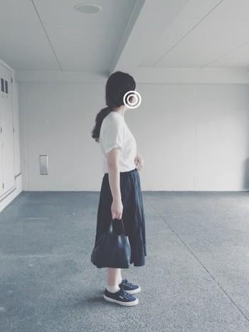 細かいギャザーの入ったフェミニンな黒いスカート。あえてTシャツやスニーカーと合わせることで、モードな雰囲気に。
