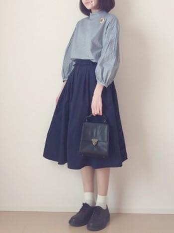 ふんわりとしたラインがかわいらしい膝丈のスカートに、クラシカルなハリ感のあるブラウスをインすれば、上品で控えめな雰囲気に。胸元のブローチが華やかさを加えてくれています。