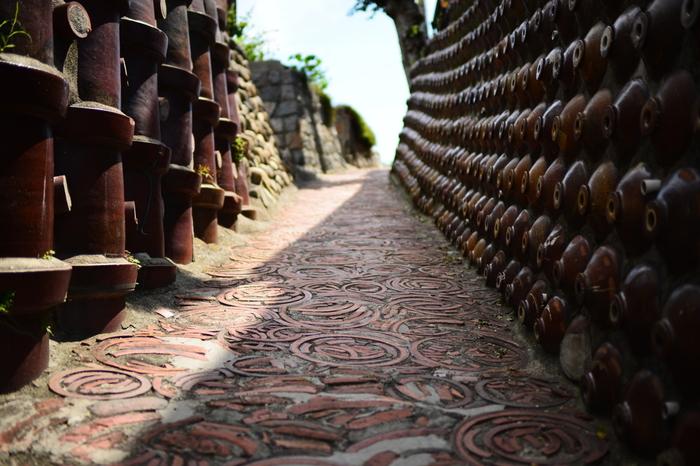 土管焼成時にできる廃材「ケサワ」を敷き詰められた地面と、土管と焼酎ビンで埋め尽くされた壁面もつ土管坂は、やきもの散歩道を代表する景勝地です。土管坂の名前の由来となっている壁の土管は明治期に、焼酎ビンは昭和初期に造られたものです。ここは、窯業で栄えていた往時の繁栄ぶりを今に伝えています。