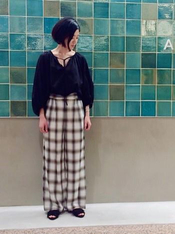 女性らしいギャザーブラウスで、程よい肌見せがポイントのスタイル。レトロなチェック柄パンツを、黒のトップスとサンダルで挟めば、コーデがきゅっと引き締まります。これくらい大胆なワイドパンツなら、トップスの裾はINするのが正解◎