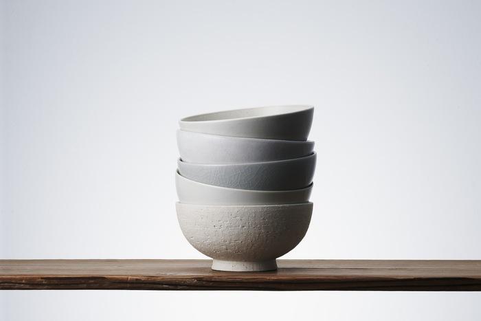 持った時に自然と手に馴染むように考えられた飯茶碗。有田、清水、信楽、瀬戸、益子という異なる日本の陶磁器の名産地でこの同じ形状の飯茶碗を作っています。同じ白色でも、それぞれの産地の土や釉薬などによって5通りの表情を楽しむことができます。