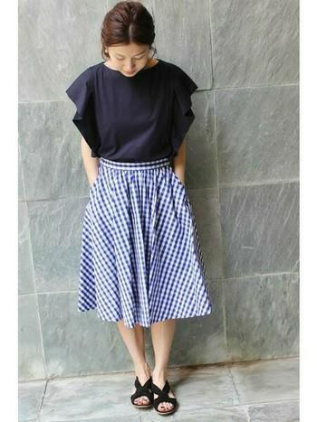 ギンガムチェックのギャザースカートと袖フリルが印象的な大人カジュアルコーディネート。歩くたびに揺れるスカートの裾が上品でとっても爽やか。
