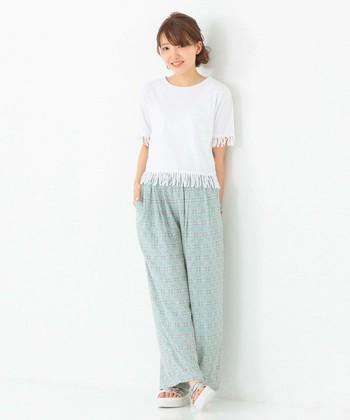 夏らしいさわやかな柄とカラーが特徴のパンツに、袖と裾のフリンジが今年っぽいカットソーがお似合い◎やわらかい素材感と色味が女性らしさを演出するスタイル。