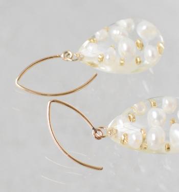 ドロップ型の透明樹脂に、淡い輝きを放つ淡水パールをそっと閉じ込めた雫(しずく)ピアス。 しずくの中でゆったり泳ぐように散りばめられた真珠と小さなゴールドビーズたち。そんな美しい一瞬を切り取って、時間を止めたようなデザインが魅力のアクセサリーです。
