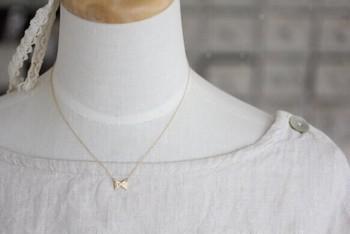 """""""三角リボンのネックレス""""。小さな三角がふたつ重なってできた、ちょこんとかわいらしいリボンモチーフのネックレス。華奢なネックレスは、女性らしさを引き出してくれるアイテムです。"""