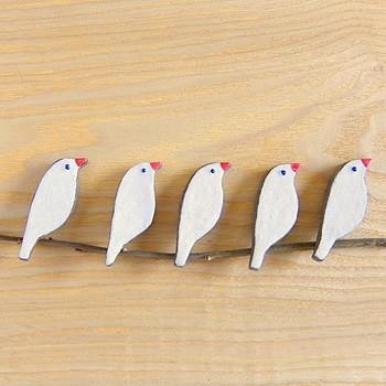 """""""文鳥の陶器ブローチ""""。素朴な表情が愛らしい、手描きの文鳥のブローチ。陶器で作られているので、ほっこりとあたたか。見ている方も、思わず気持ちが和んでしまいますよね。"""