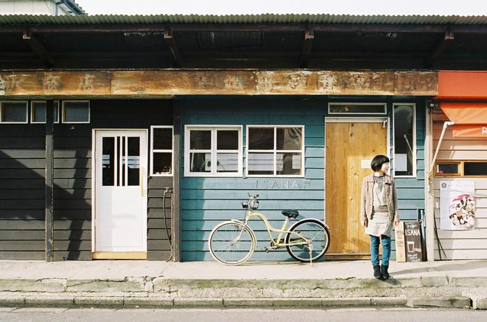 青い壁と黄色の自転車のコントラストが印象的な「ISANA(イサナ)」。オリジナルメイド家具と染め織り布の販売の他、カフェも併設。