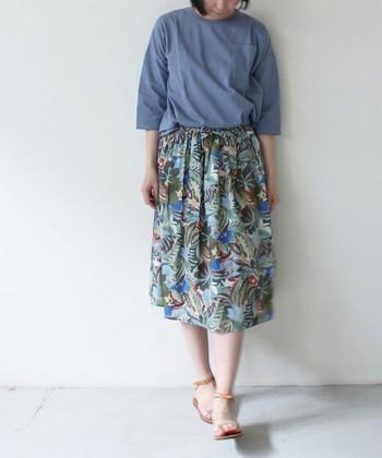 爽やかなブルーのトップス×植物柄のスカートが瑞々しい印象。足元はヌーディな抜け感を。